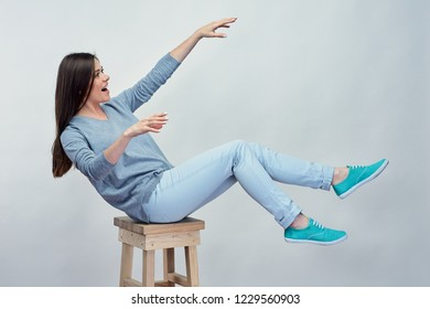 girl falls from chair in studio on grey back.