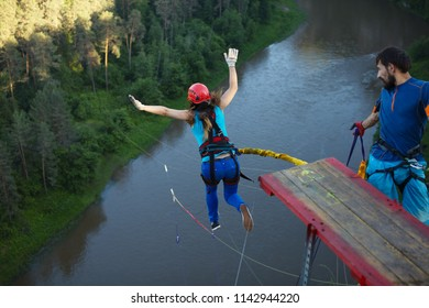 Girl falls from a great height by pushing away from the wooden platform during a jump with a rope, back view. Ropejumping.