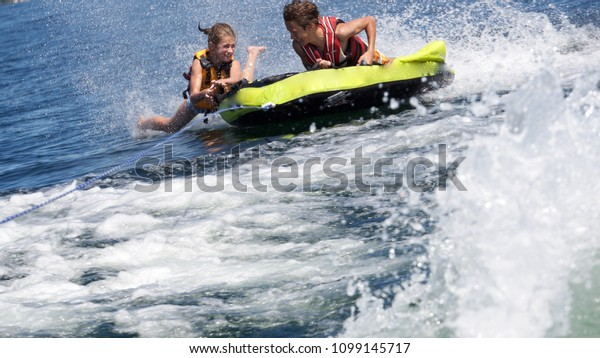 A girl falls off inner tube being pulled behind a boat in Seattle's Lake Washington while her brother holds on.