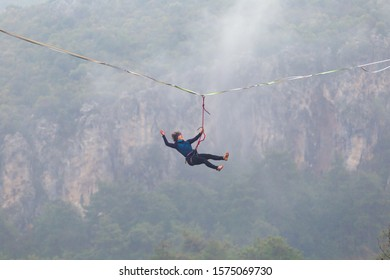 Girl falls on a stretched sling. Highline in the mountains. Woman lost her balance. Performance of tightrope walker in nature. Highliner hanging on a rope. Fall athlete.