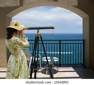 Girl in fancy dress and hat looking through telescope at the ocean from a balcony under an arch.