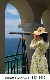 Girl in fancy dress and hat looking through telescope at the ocean from a balcony under arches.