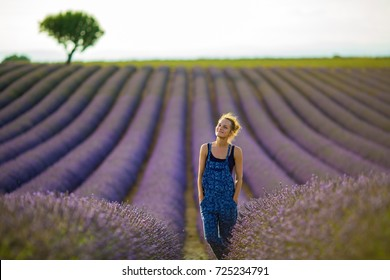 girl farmer in overalls enjoying the rays of the evening sun, standing in the midst of a ripening lavender field