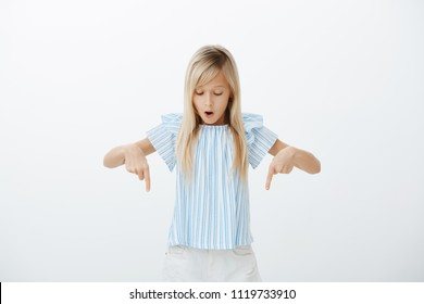Girl fascinated and excited while walking on glass floor. Portrait of amazed attractive blond young daughter in cute blue blouse pointing and looking down with dropped jaw, standing over gray wall