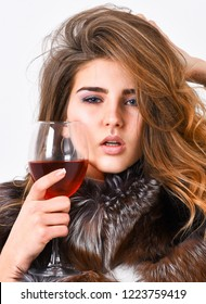 Girl fashion makeup wear fur coat hold glass alcohol. Elite leisure. Lady fashion model curly hairstyle enjoy elite wine. Wine culture concept. Woman drink wine. Reasons drink red wine in wintertime.