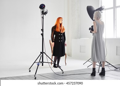 Girl fashion model and photographer are in the Studio on white background
