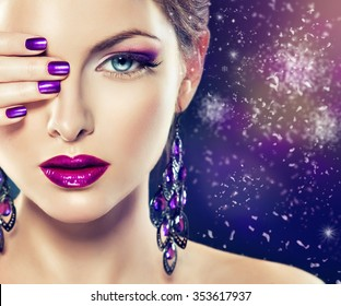 Girl fashion model with purple makeup and  lilac manicure on the nails . Long purple earrings ,  jewelry accessories . Winter snow background .