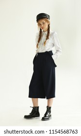 Girl in fashion trousers and a cap, full-length, studio.