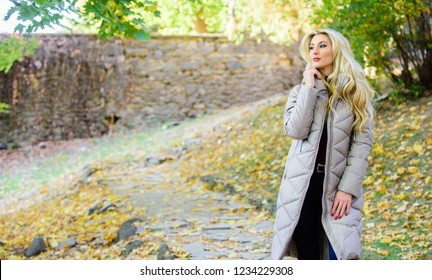 Girl fashionable blonde walk in autumn park. Woman wear warm grey jacket. Jacket everyone should have. Puffer fashion trend concept. Oversized jacket trend. Puffer jacket casual and comfortable style.