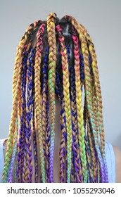 A girl with a fashionable set of multicolored braids Kanekalon. Colored artificial strands of hair. Material for plaiting braids.