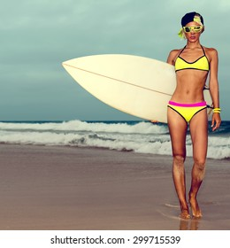 Girl in fashionable Swimwear standing on the beach with Surf board.