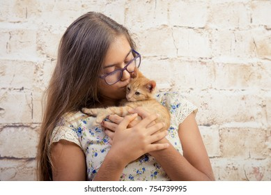 Girl with a favorite kitten. Young beautiful girl is holding a red kitten. Lovely portrait of a teenage girl with a small cat. Girl with long hair wearing glasses. funny cat