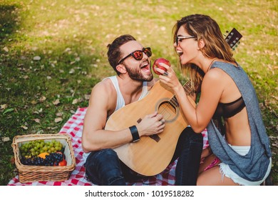 Girl feeding apple to her boyfriend on a picnic while he is playing on a guitar