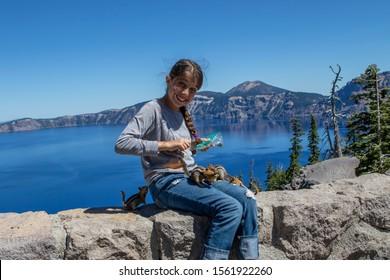 Girl feeding a chipmunks atCrater lake National park. Oregon.