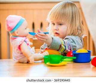 girl feeding a doll at home in the children's room