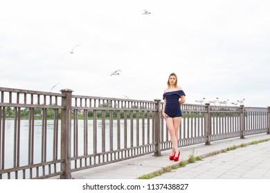 girl is feeding gulls on the embankment of the Angara River