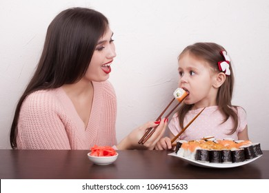 A girl is feeding her daughter a sushi of traditional Japanese food