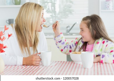 Girl feeding her mother at the kitchen