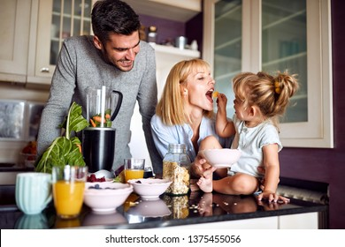 Girl feeding her mother in the morning in kitchen