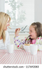 Girl feeding her mum cereal at the kitchen