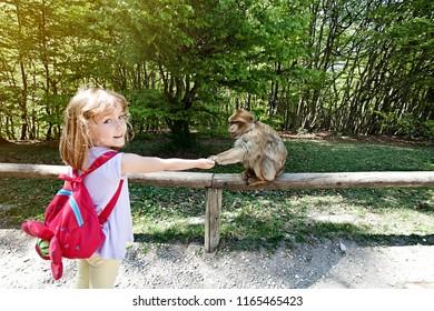 Girl feeding monkey