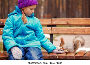 Girl feeding red squirrel in on the bench