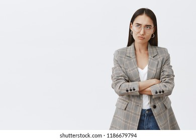 Girl feeling displeased being disappointed with ruined plans. Gloomy and moody cute adult woman in glasses and jacket, smirking and sulking, frowning from dislike while holding hands crossed on chest