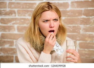 Girl feels ill suffer fever and take medicine. Pills for breaking fever. Headache and fever remedies. Woman tousled hair scarf hold glass water and tablets blister. Take medications to reduce fever.