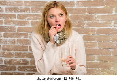 Girl feels ill suffer fever and take medicine. Headache and fever remedies. Pills for breaking fever. Take medications to reduce fever. Woman tousled hair scarf hold glass water and tablets blister.