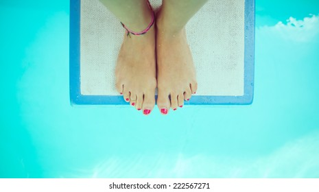 girl feet on a springboard. She is ready to jump in the water. view from above