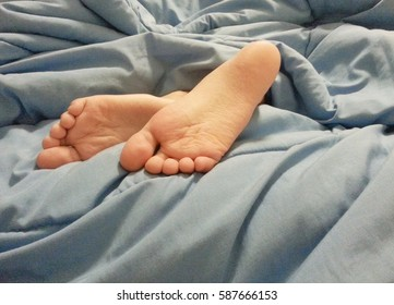 Girl feet under blue blanket