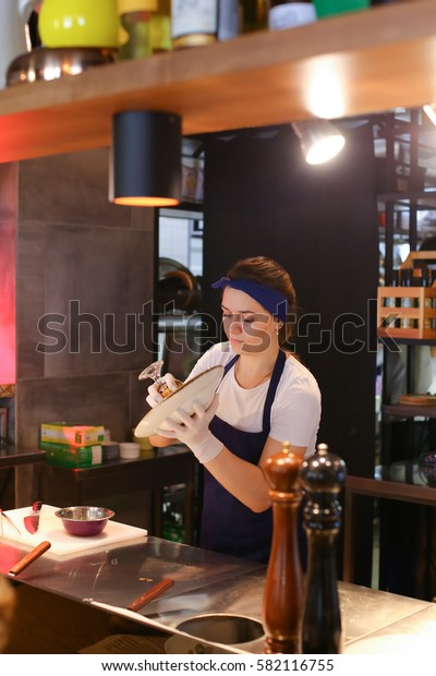 Girl female woman chef prepares dishes in the restaurant, pours into a bowl, gloved hands, a kitchen for cooking