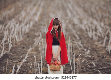 Girl in a field with a basket of apples in the hands of