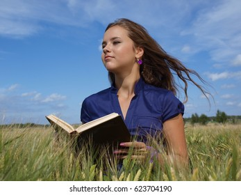 girl in a field with book on her hands
