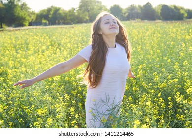 The girl in the field with flowers and pollen breathes deeply, happy about the lack of allergy.