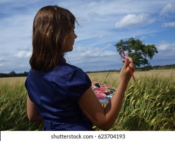 girl in a field like drawing a tree
