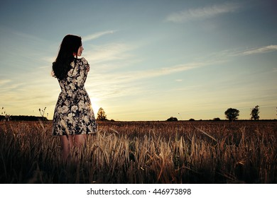 Girl in the field on sky background sunset