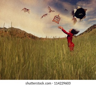 a girl in a field tossing a birdcage in the air