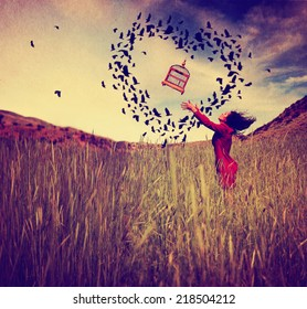 a girl in a field tossing a birdcage in the air with birds flying in the shape of a heart toned with a retro vintage instagram filter effect