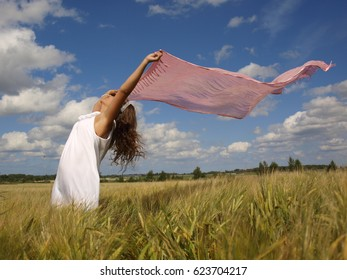 girl in a field with wind-driven a pink scarf summer outside shoot