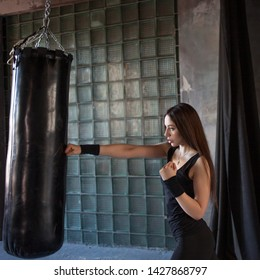 Girl fighter Boxing with punching bag, a young woman trains in the gym. Dark grunge style gym