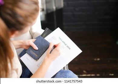girl filling visa application form, student sitting on grey chair with passport. Young fair-haired woman wearing beige T-shirt jeans holding planchette with papers writing. Concept of execution of
