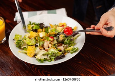 Girl fills salad with hands and cutlery