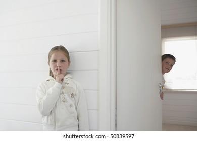 Girl with finger on lips standing by boy peeking round door