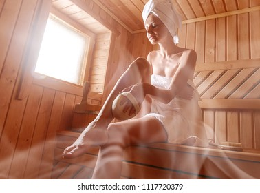 girl in a Finnish sauna doing skin peeling