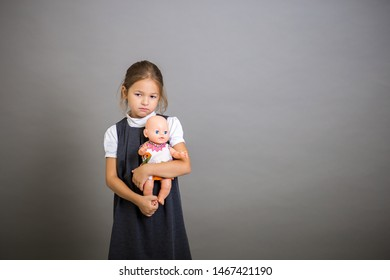 The girl the first grader embraces a doll and longs that it is necessary to go to school. Sad child
