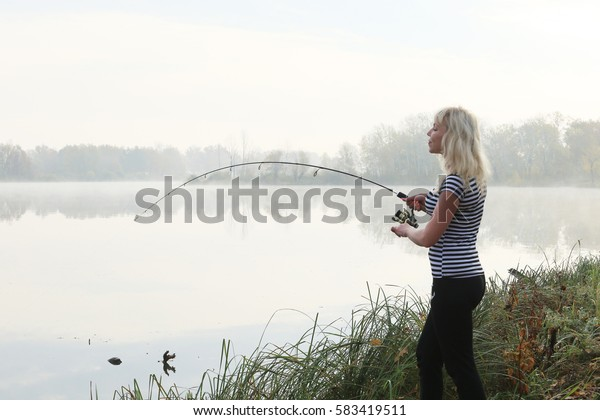 Girl fishing foggy autumn morning on the river