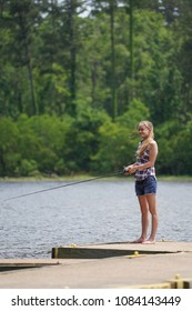 Girl fishing on a dock at a local lake, enjoying the peacefulness & views in  country setting  hoping to find a friend