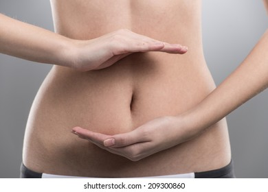girl fitness stomach on grey background. young girl holding two hands on stomach
