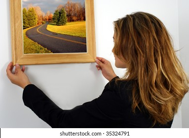 girl fixing a picture frame on the wall